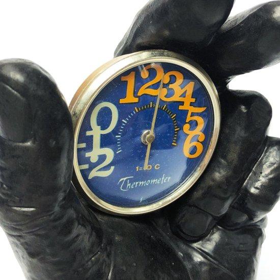 彫刻のようなセラミック製の手のオブジェが土台となっている古い温度計