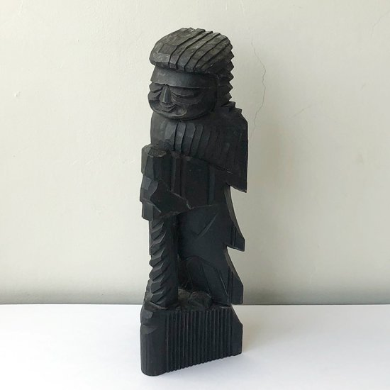 抽象的な造形や笑った表情が特徴的な古い木彫りの仏像